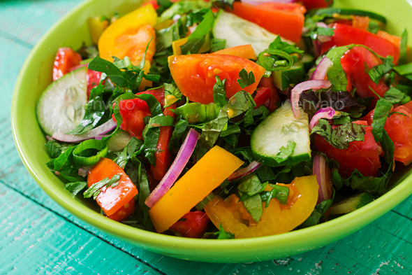 Fresh salad of tomatoes, cucumbers, peppers, arugula and red onion - Stock Photo - Images