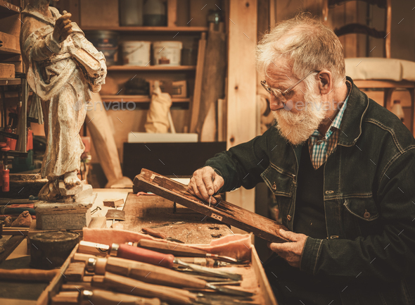 Senior restorer working with antique decor element in his workshop - Stock Photo - Images