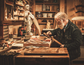 Senior restorer working with antique decor element in his workshop - PhotoDune Item for Sale