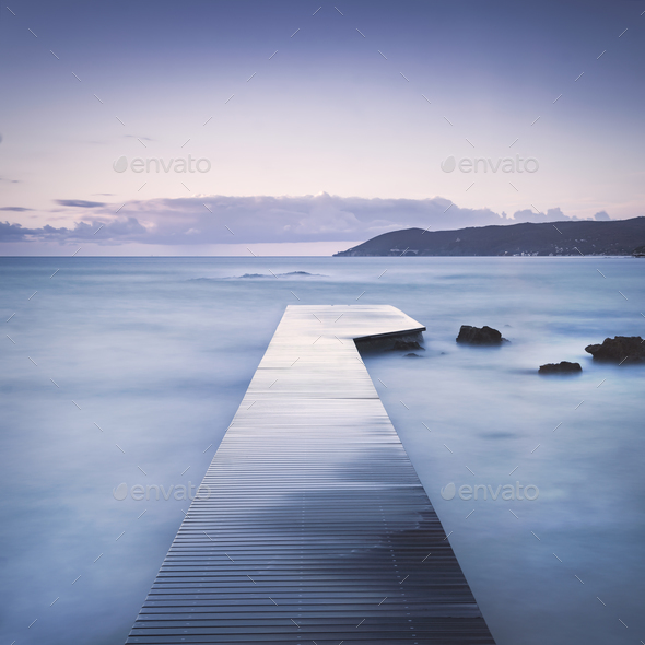 Wooden pier, rocks and sea on misty sunset. - Stock Photo - Images