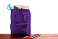 Open purple backpack with school supplies on wooden table. Back to . Close up. - PhotoDune Item for Sale