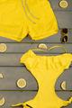 Beach accessories on wooden background. Yellow swimwear one-piece, swim shorts,