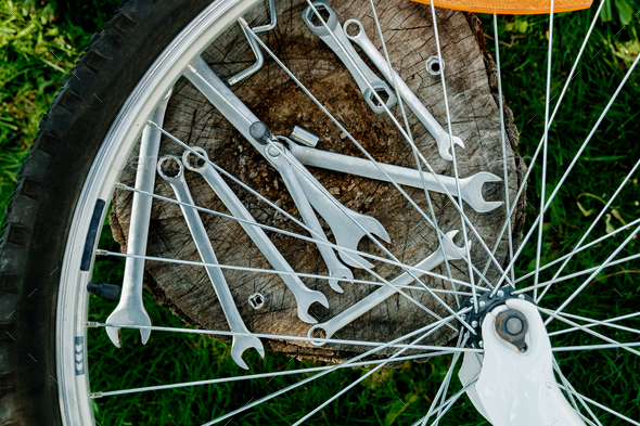 Tools, instrument for repairing bike on the wooden background outdoor wheel. Bicycle repair. - Stock Photo - Images