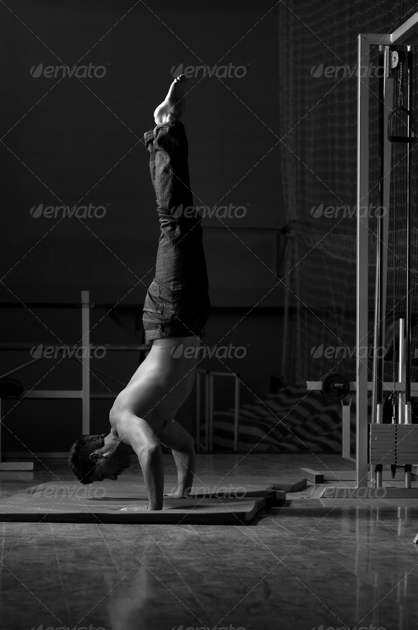 young man performing handstand in fitness studio - Stock Photo - Images