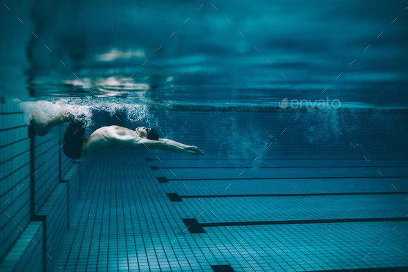 Male swimmer turning over in swimming pool - Stock Photo - Images
