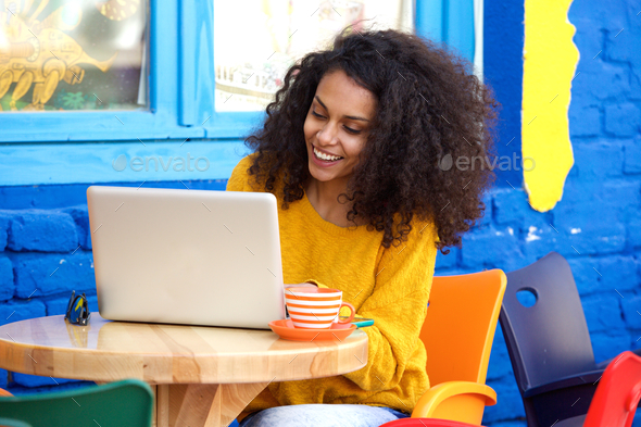 Happy young woman sitting at outdoor cafe using laptop - Stock Photo - Images