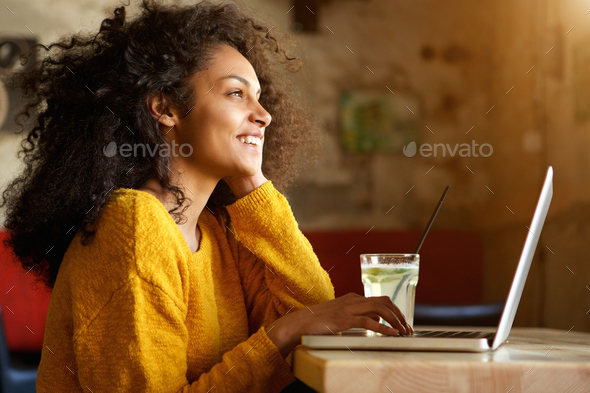 Smiling young woman sitting in a cafe with laptop - Stock Photo - Images