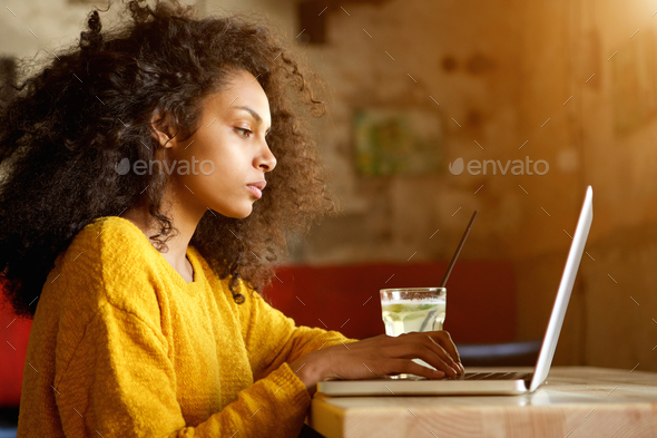 Beautiful young woman working on laptop in a cafe - Stock Photo - Images