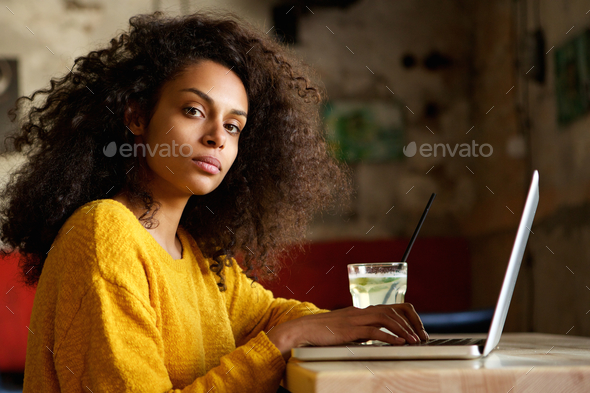 Serious young african woman working on laptop in a cafe - Stock Photo - Images