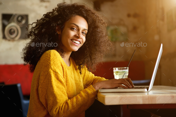 Smiling young african woman sitting in a cafe with laptop - Stock Photo - Images