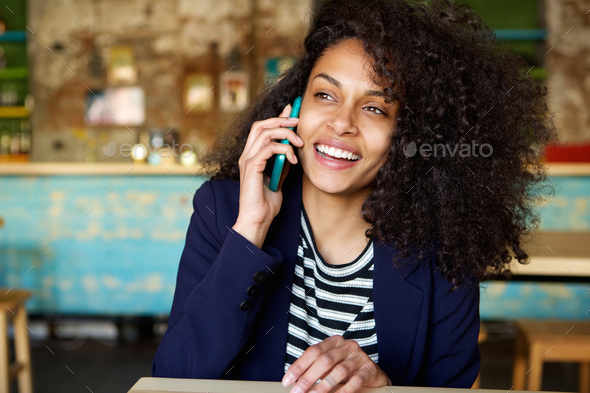 Laughing young woman talking on cellphone at cafe - Stock Photo - Images