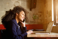 Young african woman relaxing in cafe and making phone call - PhotoDune Item for Sale