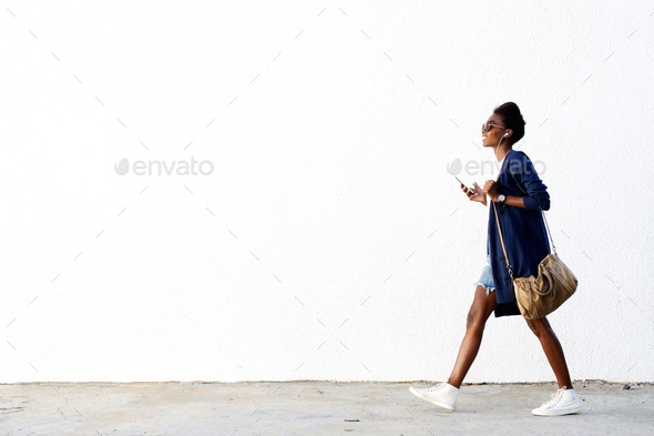 Trendy black woman listening music on mobile phone - Stock Photo - Images