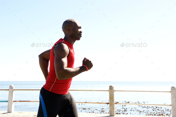 African man jogging on seaside promenade - Stock Photo - Images