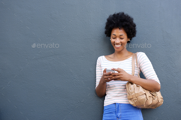 Smiling african woman with bag looking at mobile phone - Stock Photo - Images