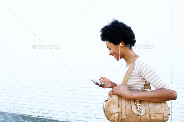 Smiling woman looking at playlist on cellphone - Stock Photo - Images