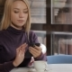 Girl Flips On Smartphone Touchscreen By Her Fingers At The Cafe - VideoHive Item for Sale