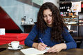 Young woman sitting at coffee shop table and writing a book - PhotoDune Item for Sale