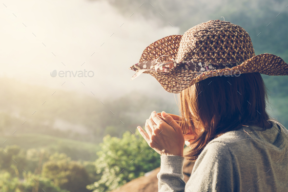 Woman holding a cup of coffee with beautiful landscape - Stock Photo - Images
