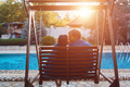Beautiful young couple sitting at the bench by the pool
