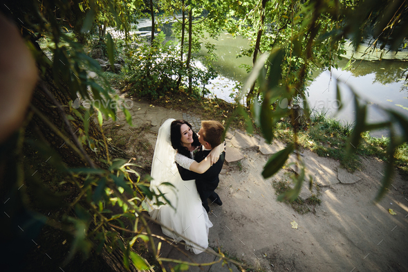 Beautiful wedding couple hugging in the park - Stock Photo - Images
