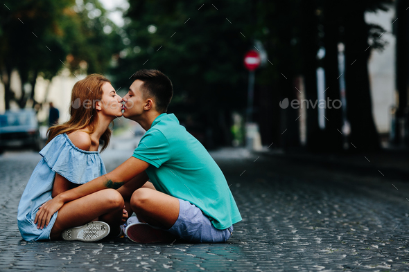 couple sitting on pavement square - Stock Photo - Images