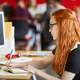 Confident female designer working at her desk in red creative office space - PhotoDune Item for Sale