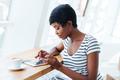 Attractive african businesswoman using tablet amd having coffee break - PhotoDune Item for Sale