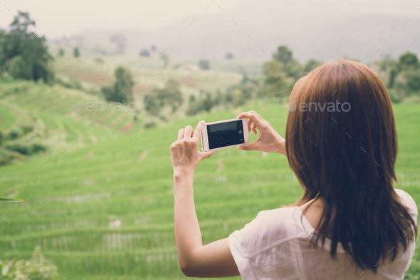 Young woman traveler taking photo with smartphone - Stock Photo - Images