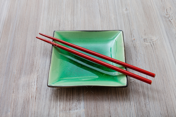 green square saucer with red chopsticks on gray - Stock Photo - Images