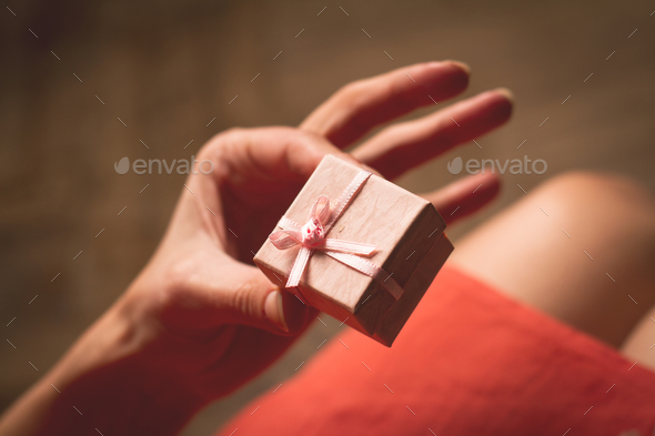 Woman holding in her hand a very small pink gift box above her k - Stock Photo - Images