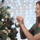 Beautiful Fashionable Girl In a Green Dress With Red Lips Decorates The Christmas Tree - VideoHive Item for Sale