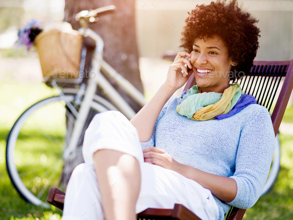 Charming young woman in summer park with mobile - Stock Photo - Images