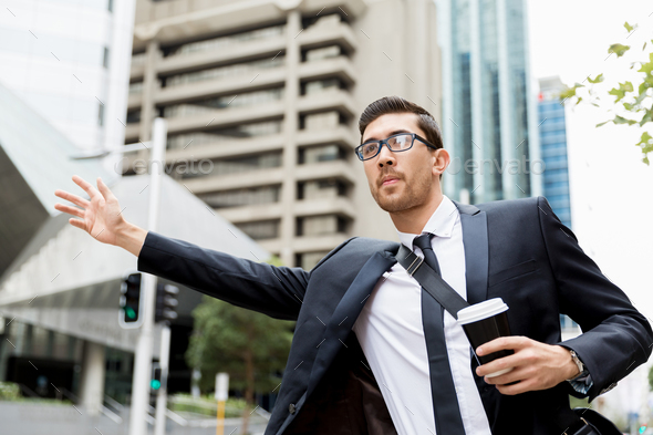 Young businessmen hailing for a taxi - Stock Photo - Images