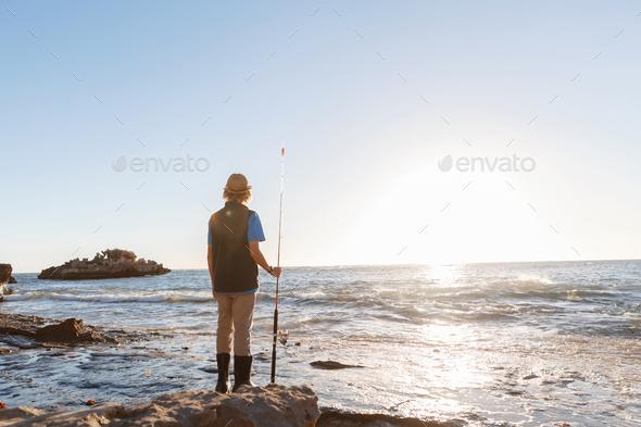 Teenage boy fishing at sea - Stock Photo - Images