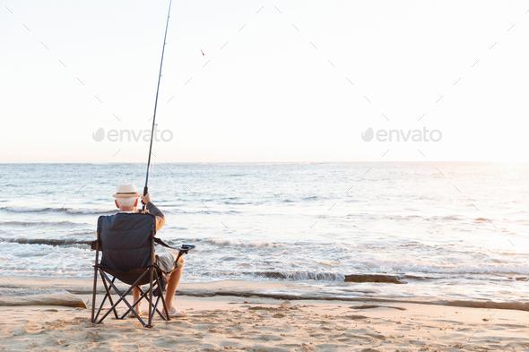 Senior man fishing at sea side - Stock Photo - Images