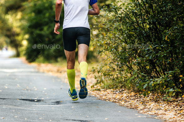 young male athlete running in autumn forest - Stock Photo - Images