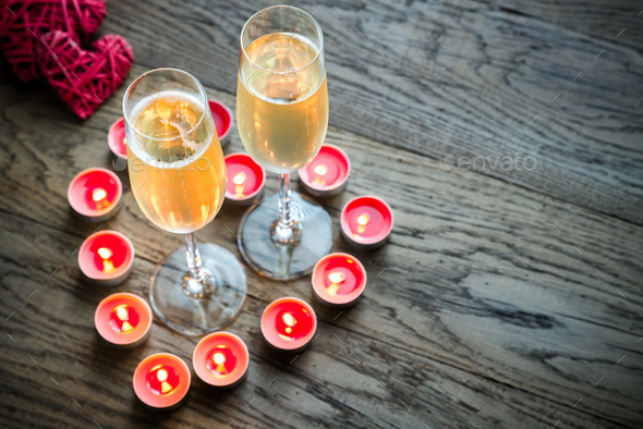 Two glasses of champagne inside of burning candles - Stock Photo - Images