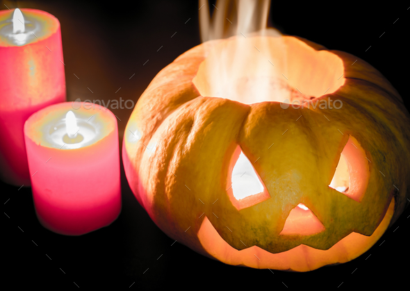 Glowing halloween pumpkin in candlelight - Stock Photo - Images