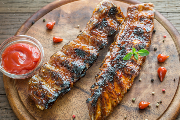 Grilled pork ribs with tomatoes on the wooden board - Stock Photo - Images