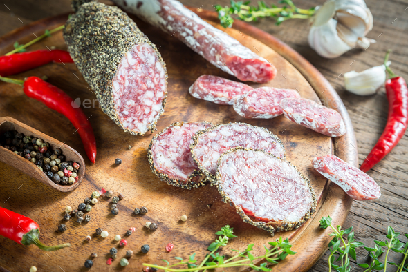 Slices of saucisson and fuet on the wooden board - Stock Photo - Images