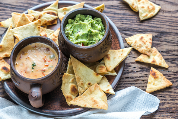 Bowls of guacamole and queso with tortilla chips - Stock Photo - Images