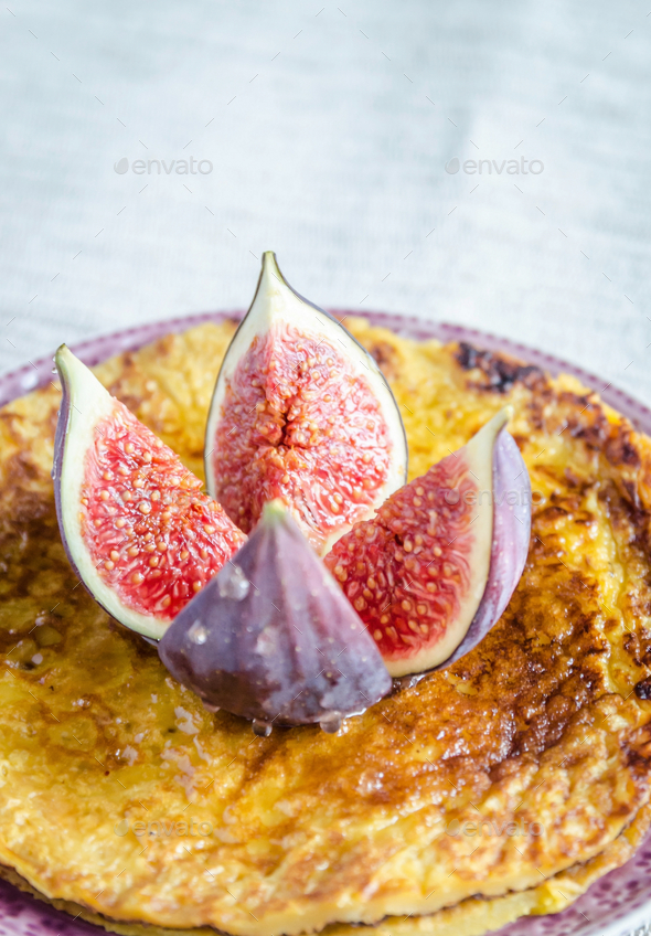 Pile of pumpkin crepes decorated with fresh fig - Stock Photo - Images