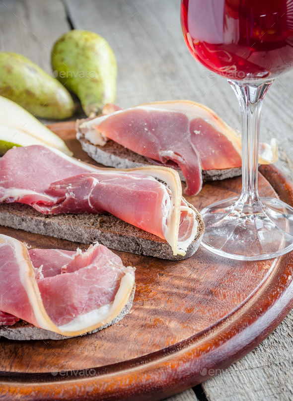 Slices of italian ham on the wooden board - Stock Photo - Images