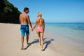 Honeymoon couple holding hands walking on beach - PhotoDune Item for Sale