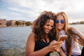 Female friends using smart phone by the lake - PhotoDune Item for Sale