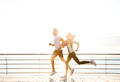 Young sporty couple running over wooden pier - PhotoDune Item for Sale