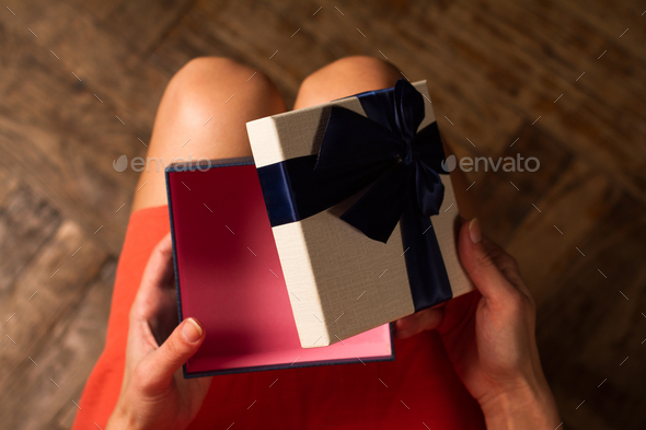 Woman opening a cardboard gift box with blue ribbon - Stock Photo - Images