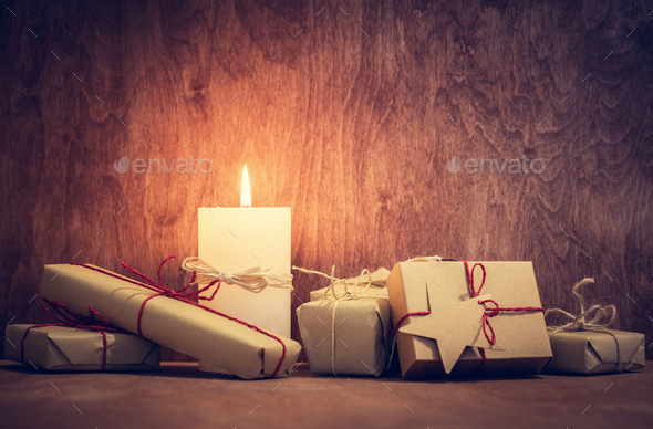 Chistmas presents, gifts with a candle glowing on wooden wall background. - Stock Photo - Images