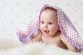 Cute baby laughing while lying under a woollen blanket. - PhotoDune Item for Sale